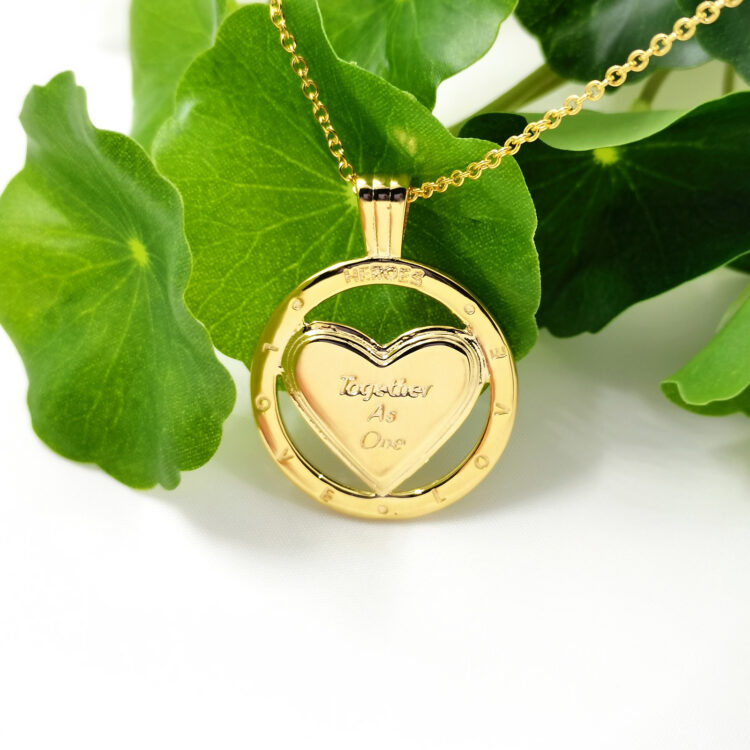 NHS Supporting 18k Gold Plated Together As One Pendant Necklace on Paper with Green Leaves
